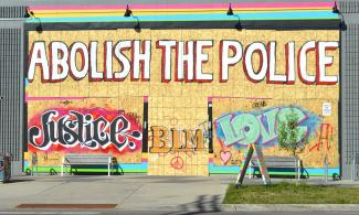 """Abolish the Police"" grafitti on a boarded-up storefront"