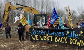 "Pipeline resistance organizers holding ""Water Gives Life. We Won't Back Down"" banner in front of backhoe"